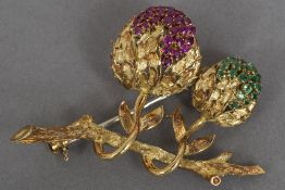 An 18 ct gold, emerald and ruby set brooch Worked as a bough issuing fruit. 4.5 cm wide.