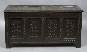 A 17th century carved oak four panel coffer The hinged rectangular top above the four carved panels