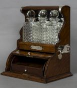 A late Victorian white metal mounted oak three bottle tantalus The decanters housed above a rising