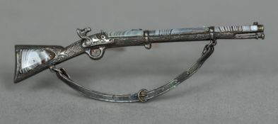 A Scottish unmarked silver agate mounted bar brooch Formed as a musket. 9 cm long.
