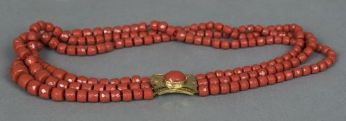 An Italian 9 ct gold mounted three strand coral necklace The beads facet cut. 65 cm long overall.