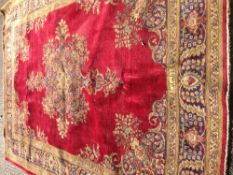 A Tabriz wool carpet The wine red field enclosing a central cruciform medallion within arabesque