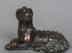 A Chinese cast bronze scroll weight Modelled as a recumbent temple lion. 7.5 cm wide.