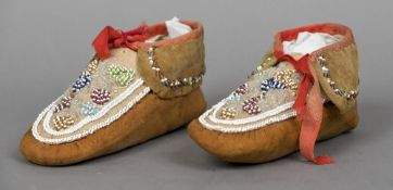 A pair of American Indian moccasins Of typical form, with bead work decorations. Each 22 cm long.