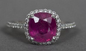 An 18 ct white gold diamond and ruby ring The central claw set ruby above the diamond filled shank.