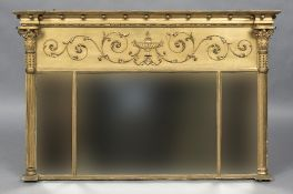 A 19th century gilt framed triptych overmantel mirror The frieze worked with an urn issuing