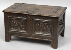 A 17th century oak child's coffer The metal strapped hinged rectangular top above carved panels,