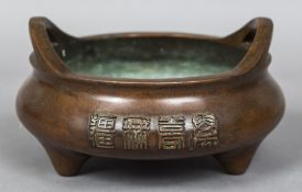 A Chinese cast bronze twin handled censor The sides with calligraphic text,