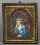 A 19th/20th century portrait miniature of a young woman seated at a table with a book Pressed brass