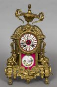 A 19th century gilt mantel clock Surmounted with ram's mask and urn finial above the painted