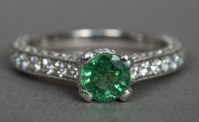 An 18 ct white gold diamond and emerald ring The central claw set emerald above the diamond set