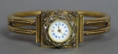 An 18 ct gold lady's bangle form wristwatch The white enamelled dial with Arabic numerals set in a