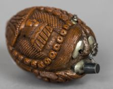 A 19th century carved coquilla nut snuff bottle Carved with the heads of three dignitaries.