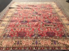 A Tabriz wool carpet The wine red field extensively filled with fronds,