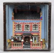 A Victorian townhouse diorama Mounted in an ebonised glazed case. 36.5 cm high.