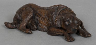A 19th century Black Forest carved wood model of a recumbent hound Naturalistically carved.