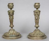 A pair of 19th century silvered bronze candlesticks Each with a florally cast drip-pan above triple