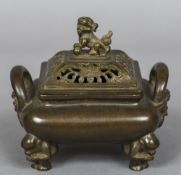 A Chinese cast bronze twin handled censor and cover The pierced cover with temple lion finial,