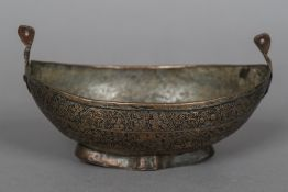 A 17th century copper Kashkul Of navette form, worked with foliage designs. 23 cm wide.