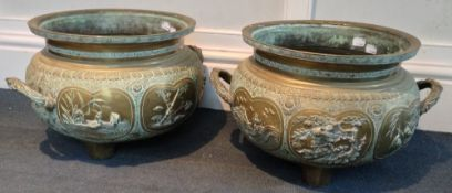 A pair of 19th century Japanese cast bronze planters Each worked with relief panels on a scrollwork
