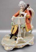 Cellospieler mit Notenblatt auf Rocaillensockel sitzend, im Barock-Stil, bunt bemalt, H 16 cm, FM