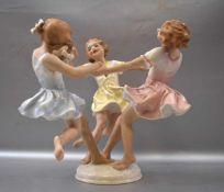 Kinderreigen drei tanzende Mädchen, auf rundem Sockel, bunt bemalt, im Sockel sign. K. Tutter, H