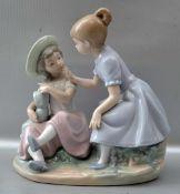 Zwei spielende Mädchen auf Steinsockel sitzend, mit Puppe, bunt bemalt, H 18 cm, B 18 cm, FM Lladro