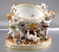 Aufsatzschale ovaler Sockel, drei spielende Puttos tragen die Schale, mit plastischen Blüten, bunt