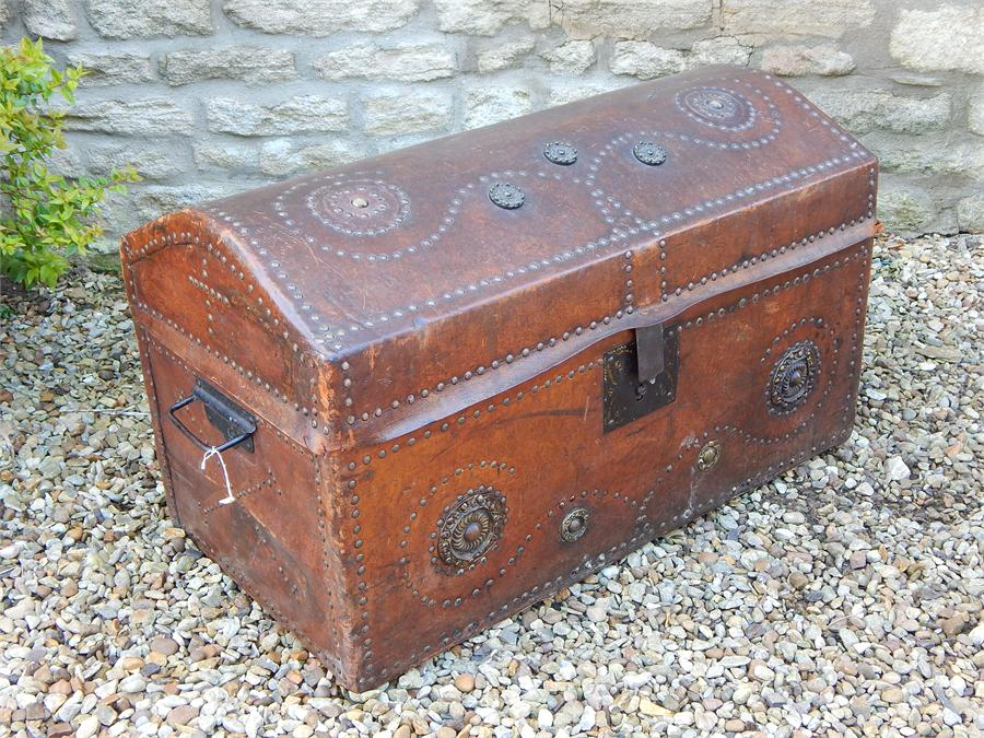 Lot 107 - Leather clad brass studded dometop trunk.