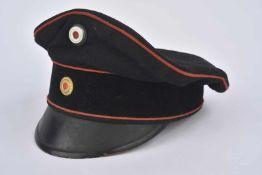 Casquette Schirmmütz bandeau velours noir, drap noir et liseré rouge. Trou de mites. Trous d'