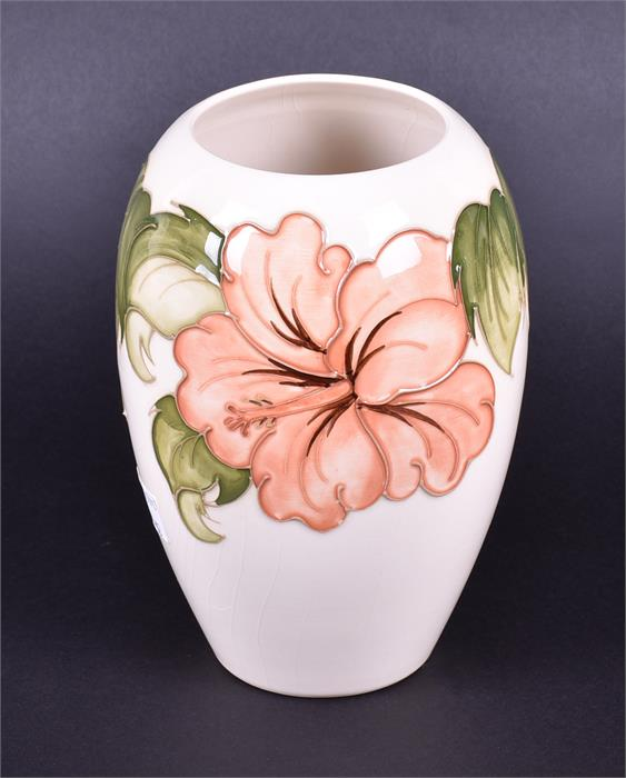 Lot 418 - A Moorcroft cream ground ceramic vase in the Coral Hibiscus pattern of baluster form with an open