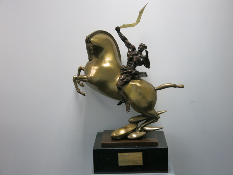 "Lot 1 - Large Bronze Sculpture on Marble Base of a Soldier Holding the Vertu Logo. Called ""A Golden Spear"