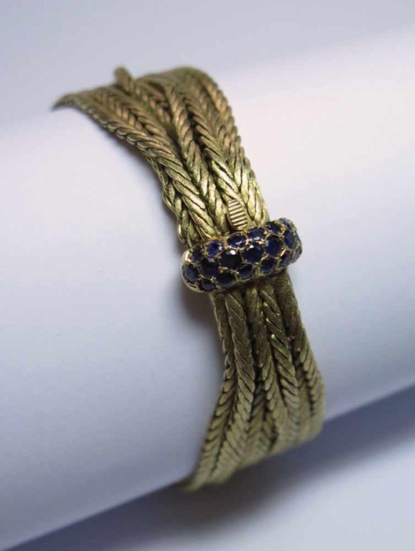 Bracelet en or jaune 750. Il est composé de sept chaînes torsadées à surface satinée. Le fermoir est