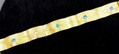 Armband 18 kt. Gelbgold, Designarbeit, Reliefdekor, mit 4 Opalen besetzt, Kastenschloss mit