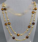 Halskette zweireihig, 14 kt. Gelbgold, mit 16 geschliffenen Tigeraugen, punziert, Gesamtgewicht 74