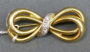Brosche 14 kt. Gelbgold, Schleifenform, 3 kl. Diamanten, um 1940, ca. 4 g schwer,