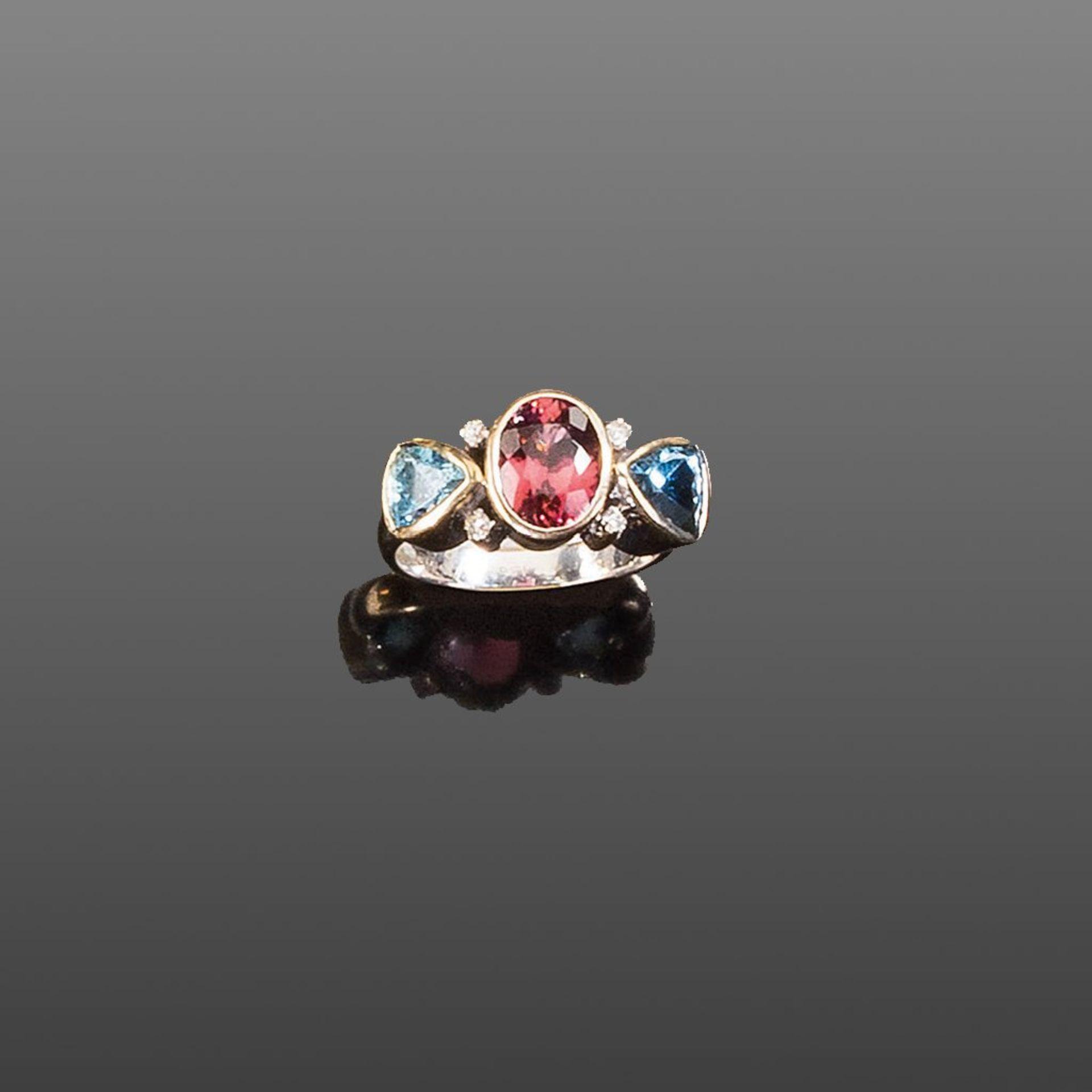 Feiner Farbsteinring. Ovaler roter Turmalin. Zwei tropfenförmige Aquamarine. Vier kleine Brillanten.