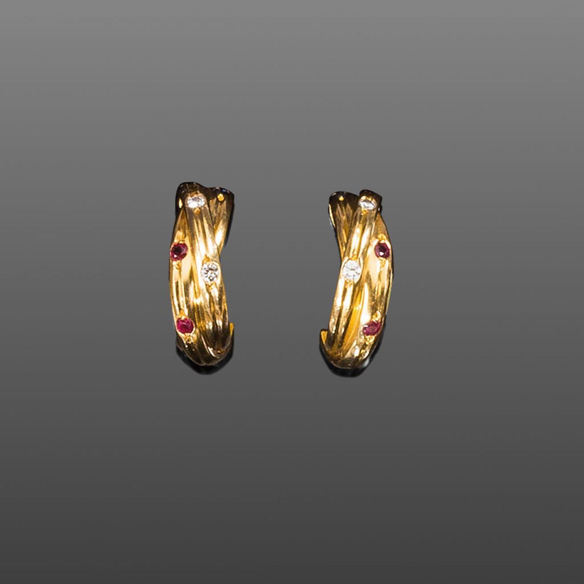 Paar Cartier-Ohrringe. Halbkreolen mit ca. 0,20 ct. Brillanten. Rubine und Saphire. 18 ct. GG, 12 g.