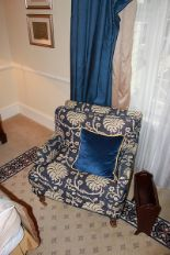 Lot 303 - A traditional easy armchair upholstered in a blue broccade fabric casters to front 700 x 800mm