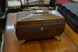 An early 19th century rosewood tea caddy, of shaped sarcophagus form, raised on floral-cast gilt-