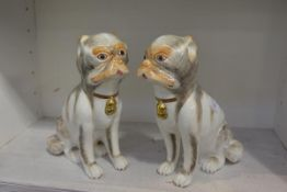 A pair of bone china models of seated pugs, 20th century, printed factory mark. 23.5cm