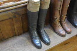 A pair of early 20th century brown top black leather riding boots, in period wooden boot trees
