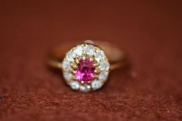 An 18ct gold ruby and diamond cluster ring, the oval ruby mounted in claw setting with surround of