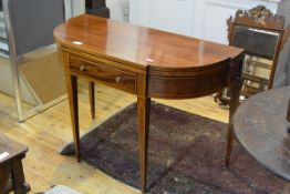 An Edwardian string-inlaid mahogany foldover tea table, in the George III taste, of shaped D-form,