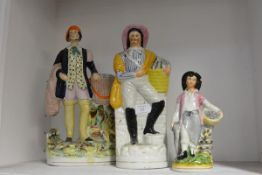 A group of three 19th century Staffordshire figures of fishermen, each carrying a basket of fish.
