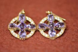 A pair of Edwardian yellow metal amethyst and seed pearl cross within a circle pendant earrings,