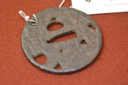 A Japanese iron tsuba, circular, with pitted surface. 7.5cm
