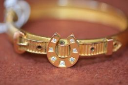 A Victorian yellow metal stiff hinged bangle with buckle style mount on a horseshoe centre set