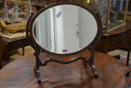 An Edwardian mahogany toilet mirror, the oval plate swivelling between scroll-carved uprights, on