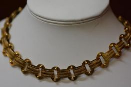 A Victorian yellow metal lozenge and oval bead link necklace with circular clip fastening. Length